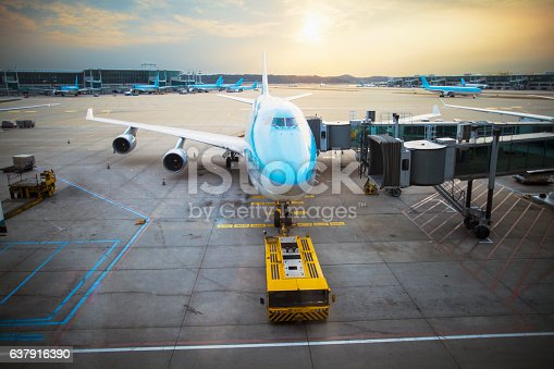 istock Jumbo jet backing out of airport departure gate at sunset 637916390