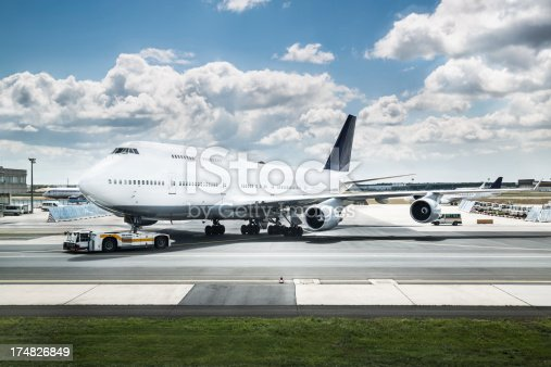 Boeing 747 (jumbo jet) gets parked nearby a runway.