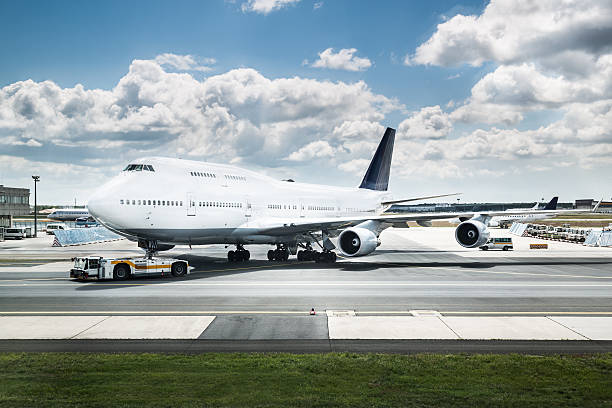 a jumbo jet gets parked nearby a runway with white clouds - luchthaven frankfurt am main stockfoto's en -beelden