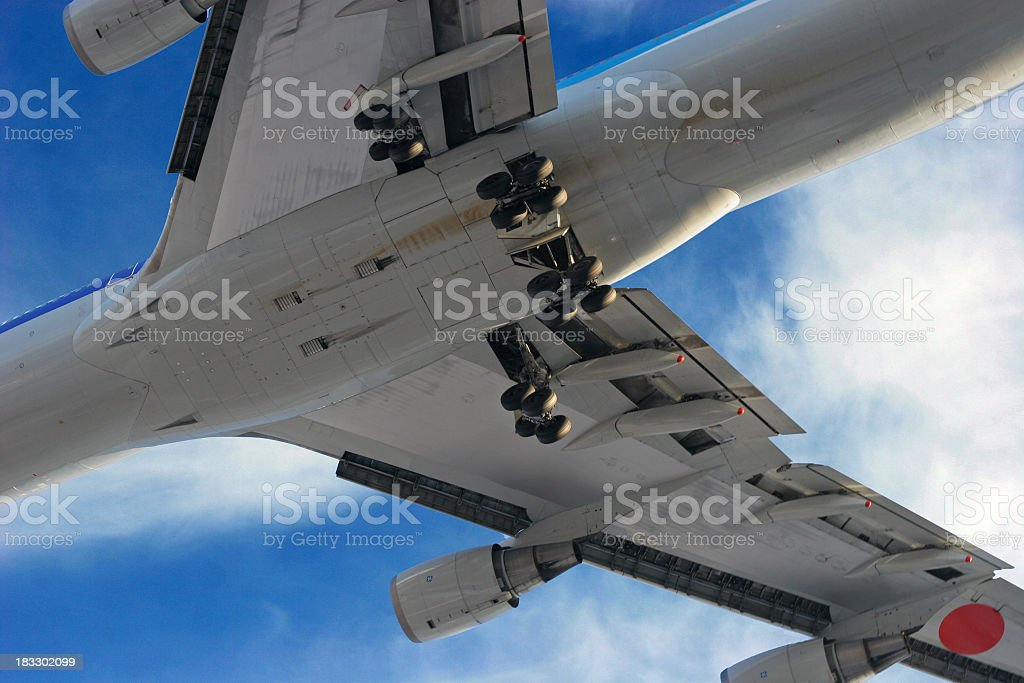 Jumbo jet plane from below on a cloudy day royalty-free stock photo