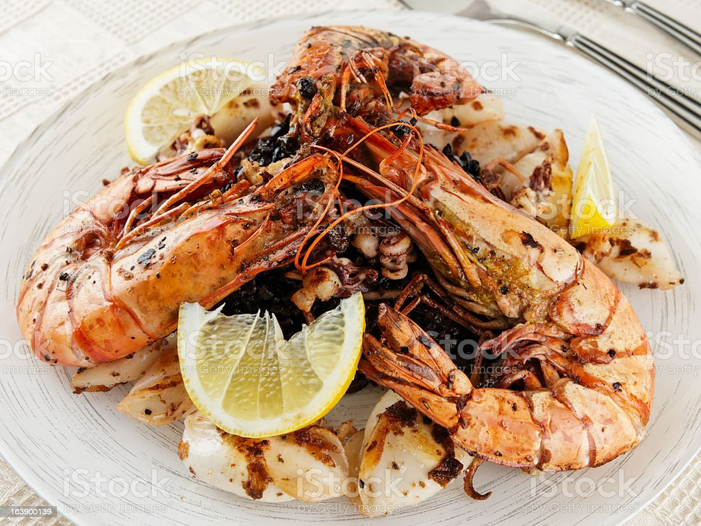 Jumbo prawns, grilled squids with black rice and lemon royalty-free stock photo