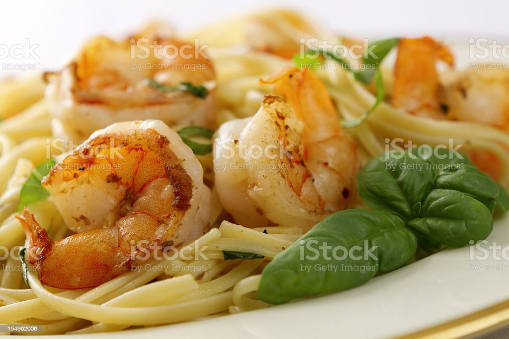 Jumbo shrimp scampi and linguini with basil on white plate stock photo