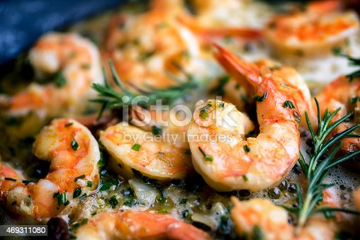 Close image of jumbo shrimp being sauteed in a pan with oregano, chive, rosemary, garlic and paprica creating Shrimp Scampi