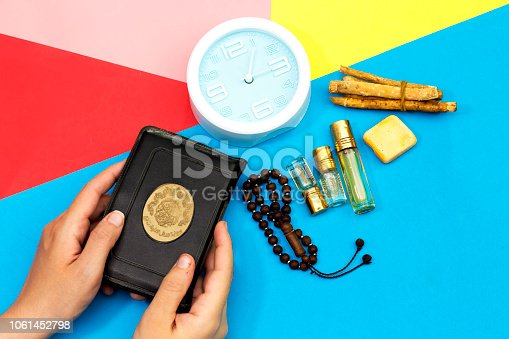 istock jummah mubarak time, woman holding holy book of muslims and rosary, siwak, perfume on colorful background 1061452798
