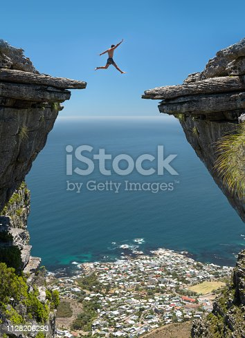Athletic man jumping the gap between two rocks over a 1000m high cliff with Camps Bay, Cape Town below. Nikon D850. Converted from RAW.