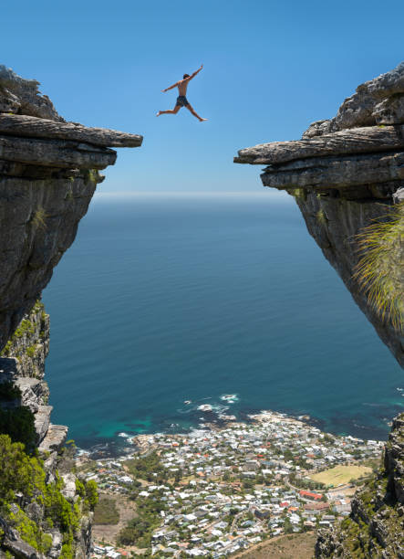 Jump! Believe in yourself Athletic man jumping the gap between two rocks over a 1000m high cliff with Camps Bay, Cape Town below. Nikon D850. Converted from RAW. apart stock pictures, royalty-free photos & images