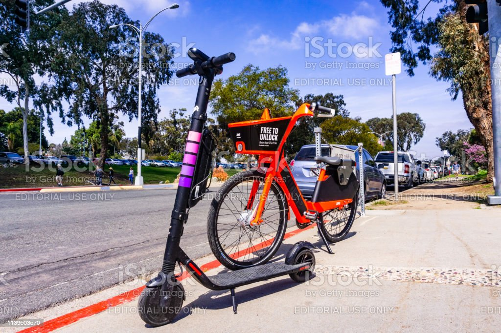 Jump Electric Bike (owned by Uber) and Lyft Escooter parked side by side on the sidewalk March 19, 2019 San Diego / CA / USA - Jump Electric Bike (owned by Uber) and Lyft Escooter parked side by side on the sidewalk, near parked near Balboa Park; Basket Stock Photo