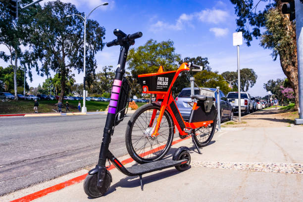 jump electric bike (owned by uber) and lyft escooter parked side by side on the sidewalk - jumping zdjęcia i obrazy z banku zdjęć