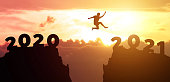 istock Jump  from 2020 to 2021 new year concept, silhouette of man jumping over barrier cliff and success with beautiful sunset background. Happy New Year 2021 use for web banner and advertisement. 1226749724