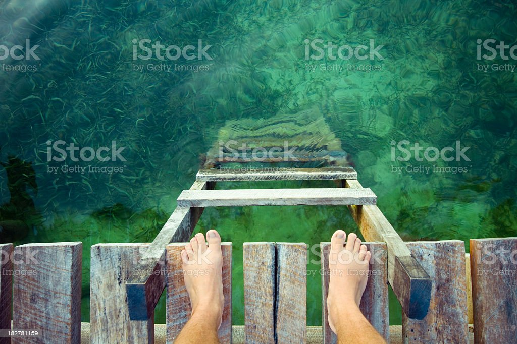 Jump In feet at the edge of a wooden dock with a ladder and clean waters below. Beach Stock Photo