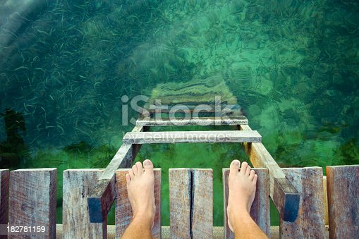feet at the edge of a wooden dock with a ladder and clean waters below.