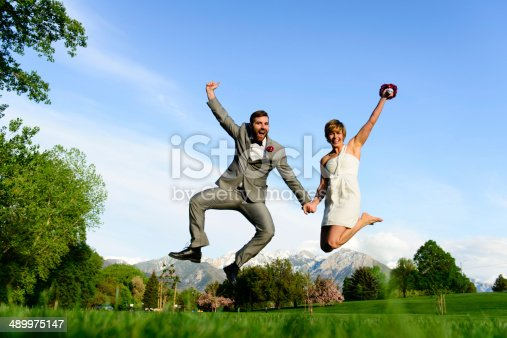Happy bride and groom holding hands and jumping in the air.   Sky, trees and mountains behind them.