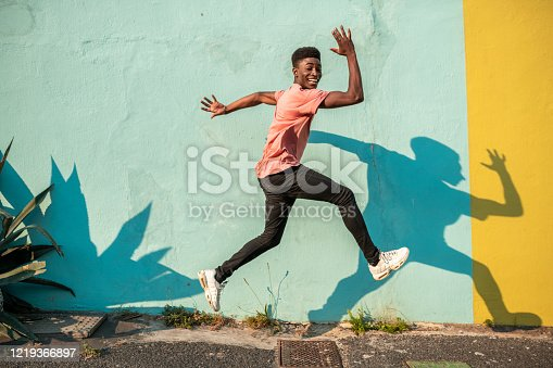 Young man dancing on the street. He has light blue wall as a background