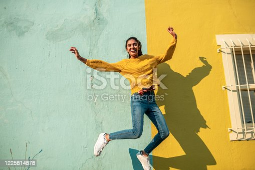 Young Indian woman jumping.She has light blue wall as a background