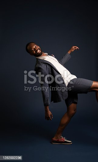 An African American man jumping on a blue background.