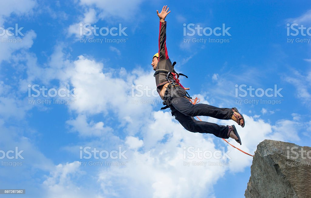 Jump rope from a high rock in the mountains. Lizenzfreies stock-foto