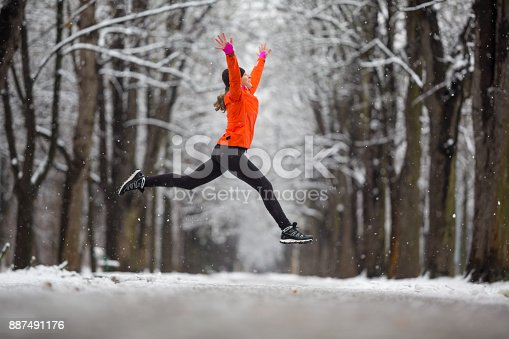 istock Jump! - side view woman jumping for joy in winter 887491176