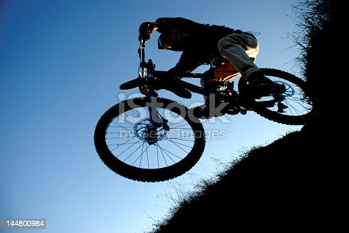 istock jump with a mountain bike - silhouette 144800984