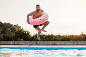 Young man enjoying time at the swimming pool jumping into the water with inflatable ring