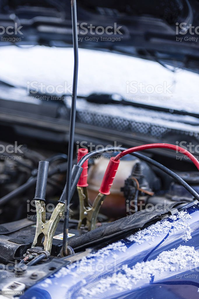 Jumper car booster cables connected to a battery stock photo