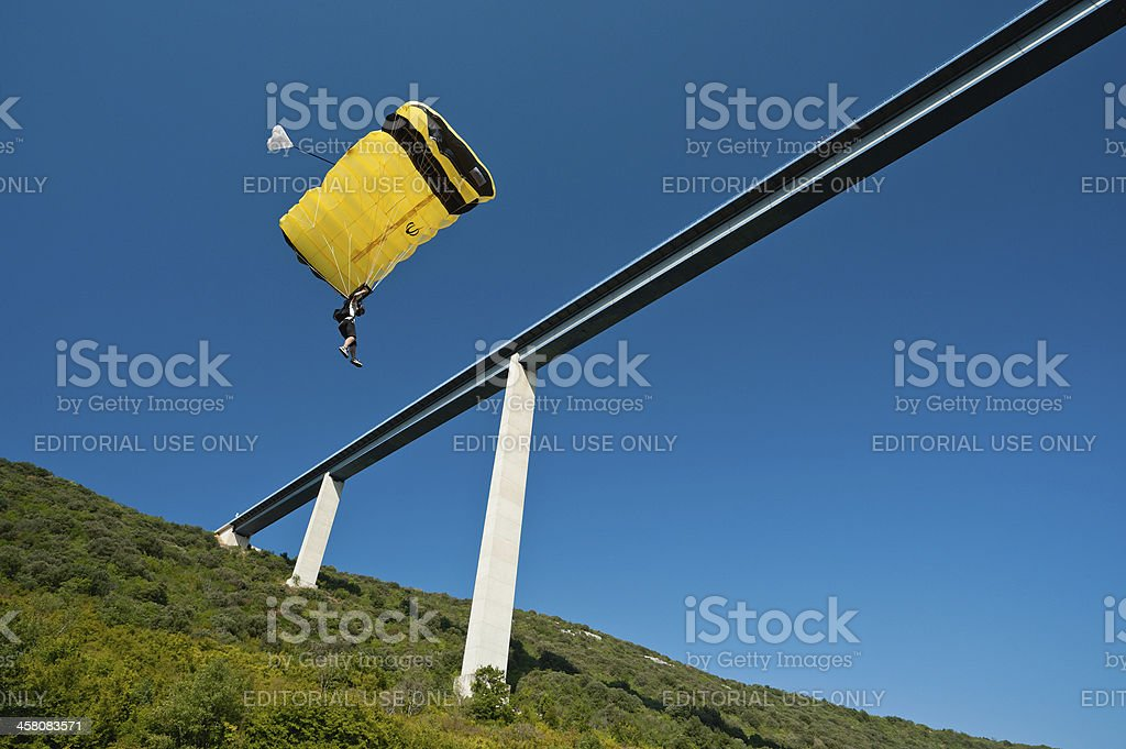 B.A.S.E. jumper descents under parachute canopy jumping off a bridge. royalty-free stock photo