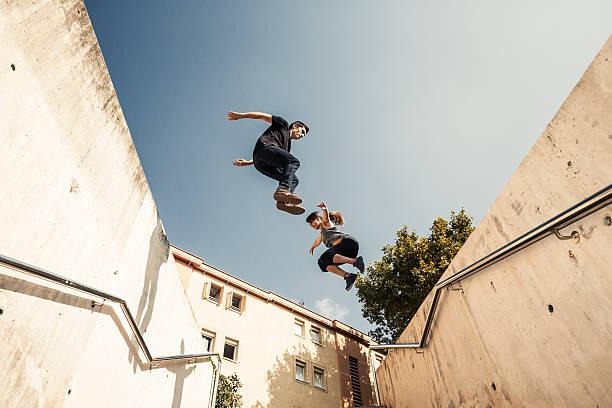 springen und üben parkour- in der stadt - parkour stock-fotos und bilder