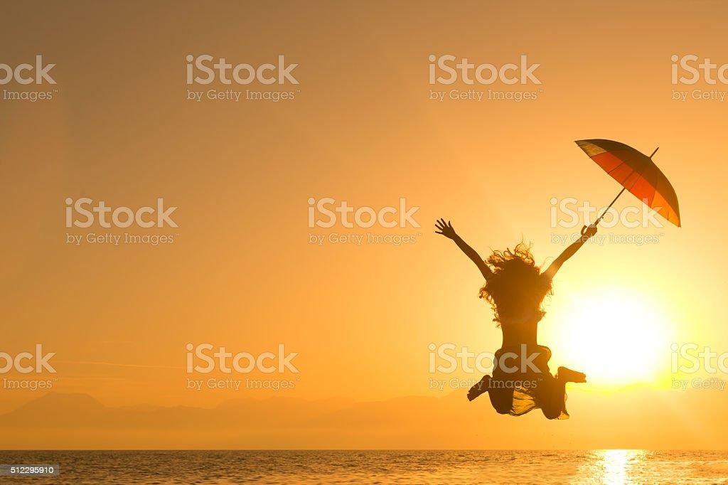 Jumping at sunset stock photo