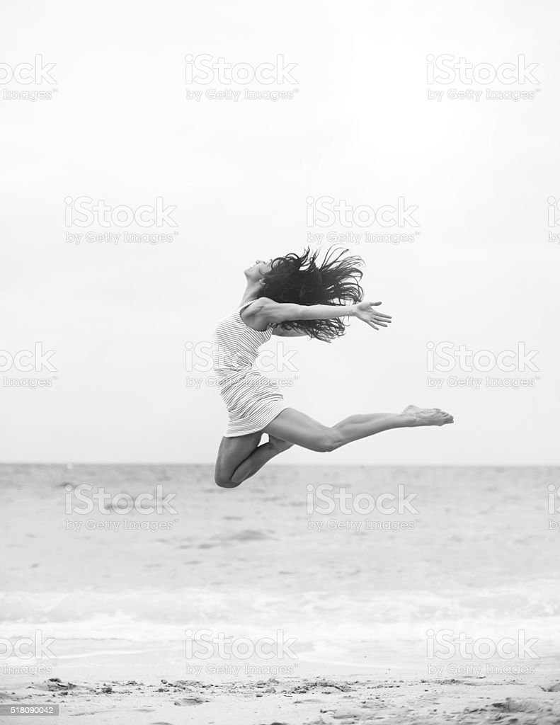Jumping at the beach stock photo