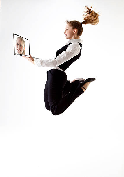 jumping business woman with laptop stock photo