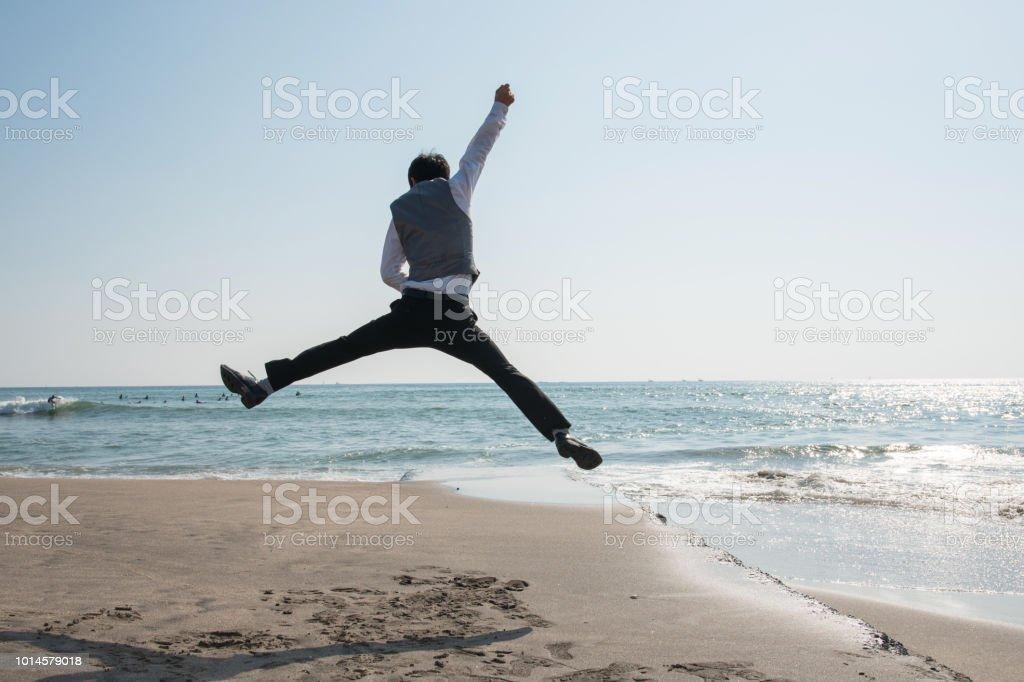 ビーチでビジネスマンをジャンプ: 都市の慌ただしさからの脱出 ロイヤリティフリーストックフォト
