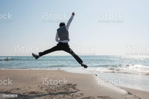 ビーチでビジネスマンをジャンプ 都市の慌ただしさからの脱出 - 1人のストックフォトや画像を多数ご用意