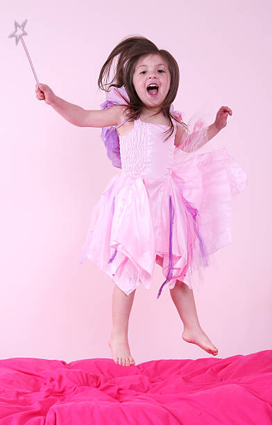 Jumping Fairy Princess A young girl jumping on the bed dressed up as a fairy princess girl bedroom stock pictures, royalty-free photos & images