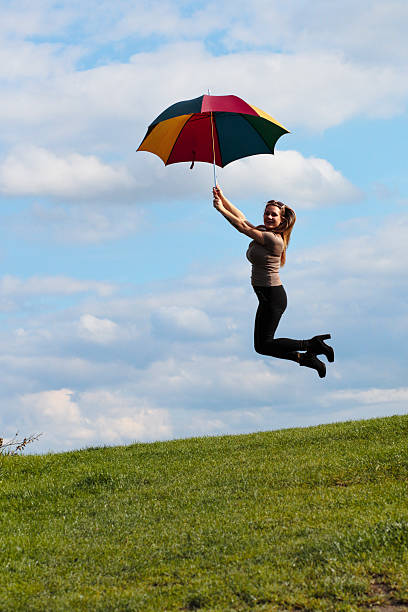 jumping with umbrella windswept shapely outdoor polish girl - whiteway polish outdoor girl stock photos and pictures
