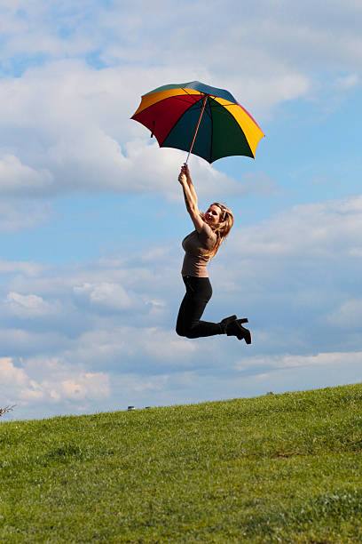 jump for joy umbrella windswept shapely outdoor polish girl - whiteway polish outdoor girl stock photos and pictures