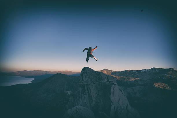 jumping for joy over lake tahoe mountains - ninja krieger stock-fotos und bilder