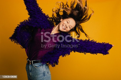 Young woman dressed in purple t-shirt and cardigan jumping in front of a yellow background.
