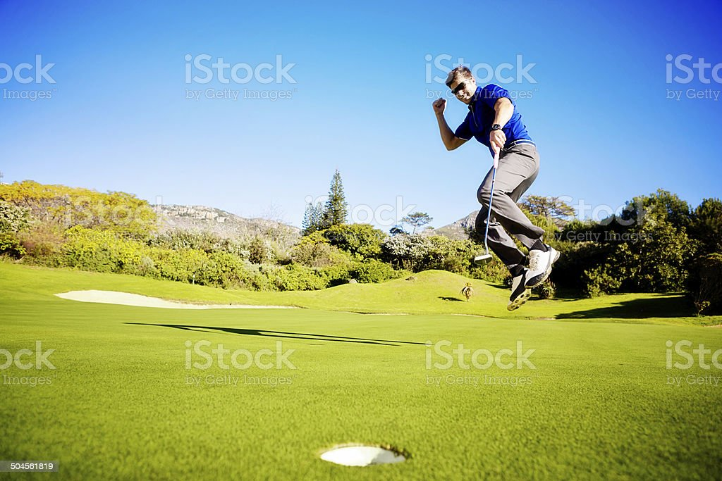 Jumping for sheer joy, a young golfer celebrates successful putt stock photo