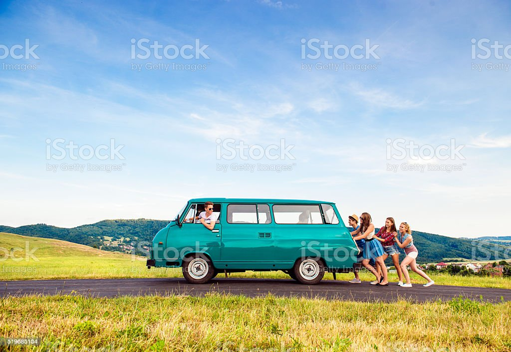 Jumping frieds with campervan, green nature and blue sky stock photo