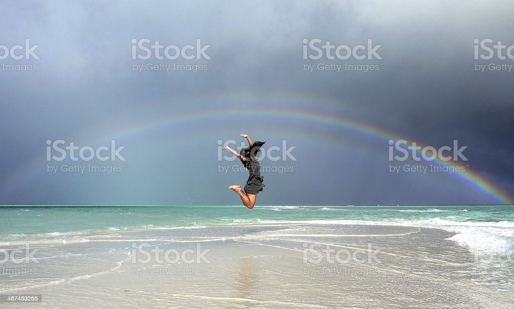 Jumping girl under a rainbow stock photo