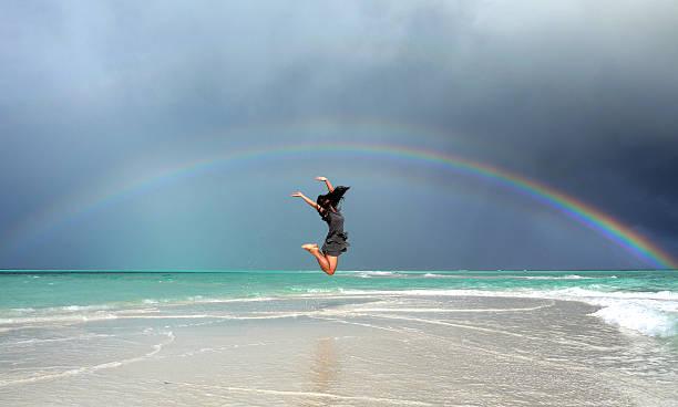 Jumping girl under a rainbow stock photo