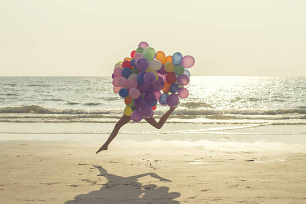 jumping girl with balloons - lightweight stock pictures, royalty-free photos & images