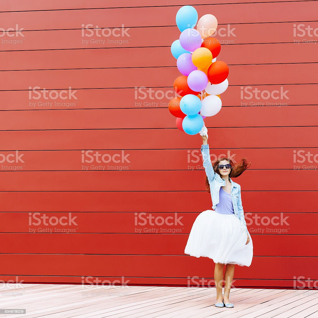 Jumping girl with colorful balloons stock photo