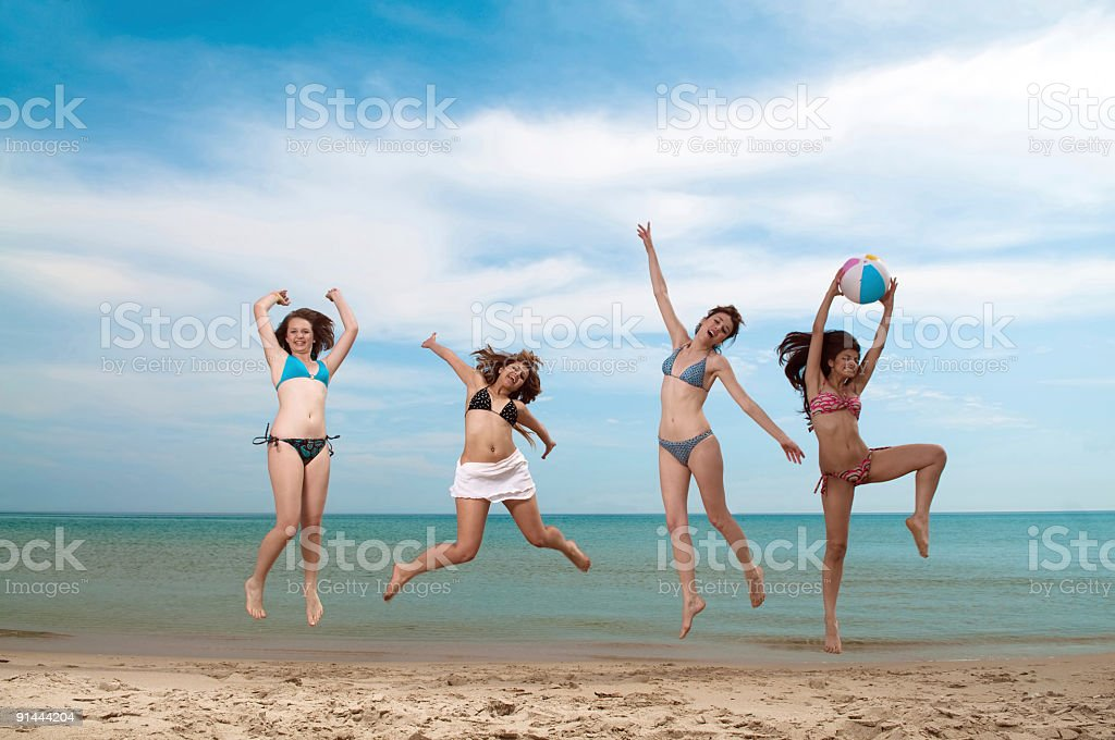 Jumping girls on the beach royalty-free stock photo