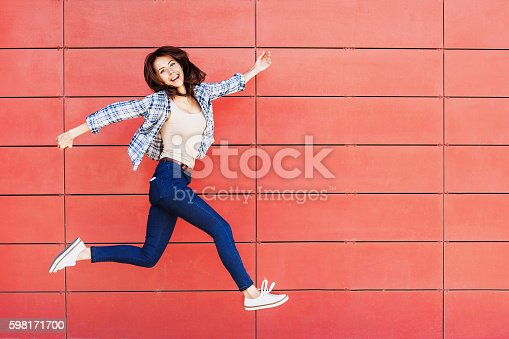 istock Jumping happy girl 598171700