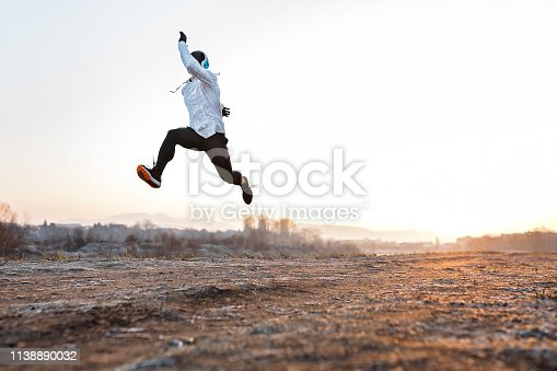 Handsome young man jumping and running by the river early in the morning