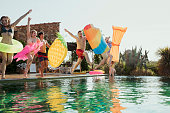 Group of friends at a pool party jumping into the water with inflatable rings.