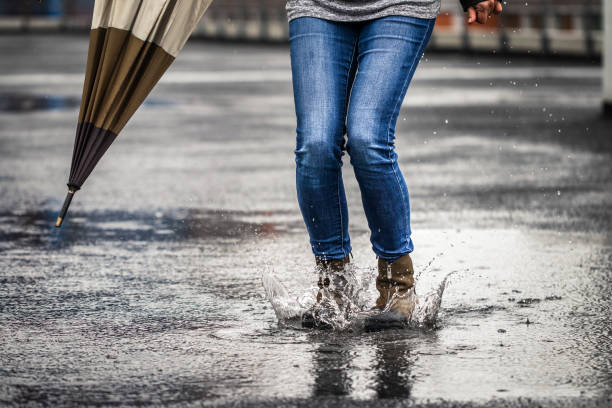 Jumping in puddle and splashing water during rain stock photo