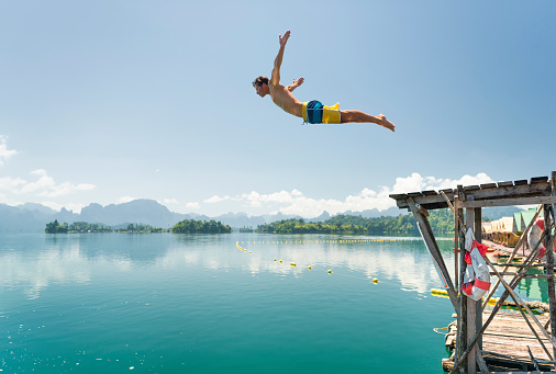 Jumping in the clear Lake Ratchaprapha, Khao Sok National Park, Thailand