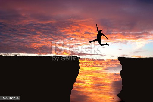 Silhouette of man jumping from one cliff to another cliff with excitement