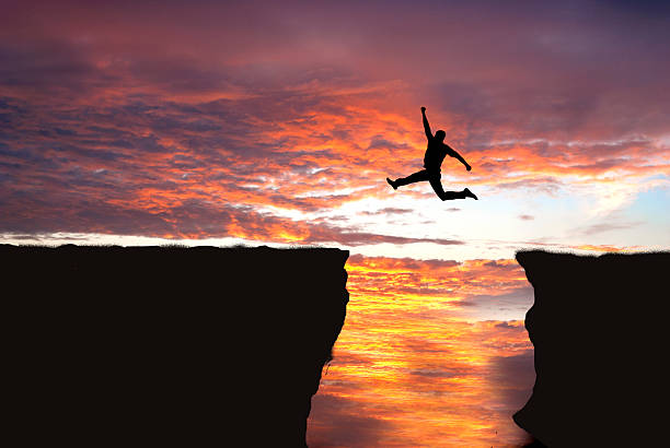 Jumping into cliff gap stock photo
